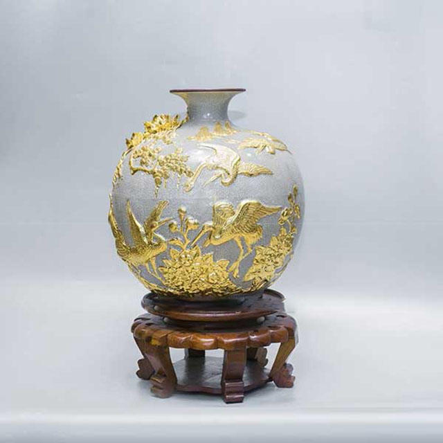 Bình hút tài lộc đắp nổi men rạn cổ mạ vàng được kết hợp chân đế gỗ để tăng tính thẩm mỹ